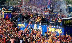 Barcelona's players celebrate on a bus with their supporters during their victory parade on the streets of Barcelona